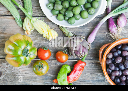taly, Tuscany, Magliano, Olives in bowl, spring onions, tomatoes, peppers and artichoke on wooden table - Stock Photo