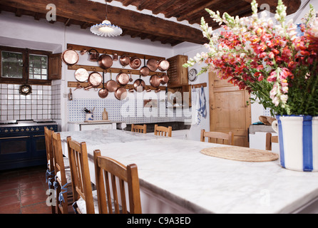 Italy, Tuscany, Magliano, View of kitchen with flowers on dining table - Stock Photo