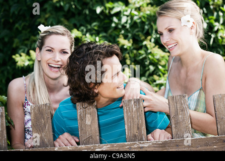 Italy, Tuscany, Magliano, Young man and women standing behind wood fence, smiling - Stock Photo