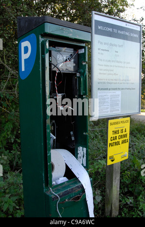Vandalised car park ticket machine with theft warning sign - Stock Photo