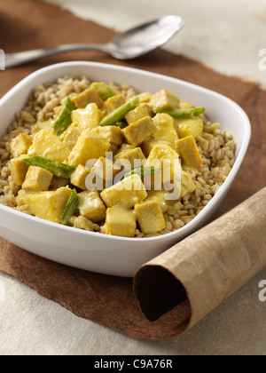 Macadamia pineapple curry over brown rice in a white bowl - Stock Photo