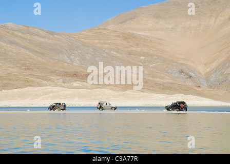 Three SUVs on an eye land in Pengong tso Lake ( an endorheic lake in the , situated at a height of about 4,350 m - Stock Photo