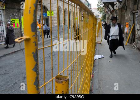 Orthodox Jews walking in a street with a fence. Mea Shearim. jerusalem. israel. - Stock Photo