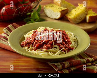 Spaghetti with meat sauce topped with Parmesan cheese and served with garlic bread - Stock Photo