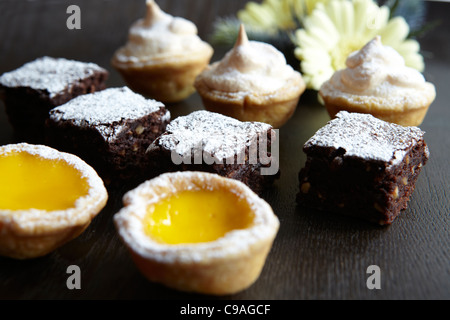 Sweet canapes, mango tarts, chocolate brownies and lemon meringue pie - Stock Photo