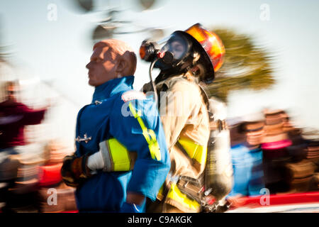 A woman firefighter carries a 175-pound mannequin backwards about 100 feet, all while wearing full firefighting - Stock Photo