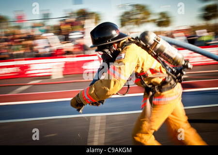 A firefighter races with a fire hose while wearing full firefighting gear and working against the clock during the - Stock Photo