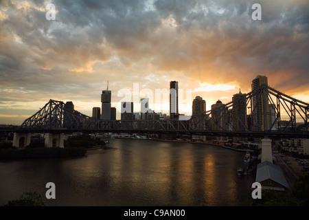 The sun sets behind Brisbane's Story Bridge and city skyline. Brisbane, Queensland, Australia - Stock Photo
