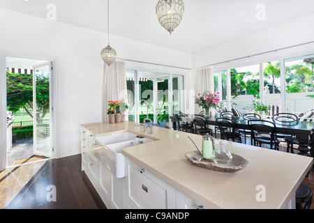 Stylish Open Kitchen With Large Dining Table Overlooking A Golf Coarse And Swimming Pool