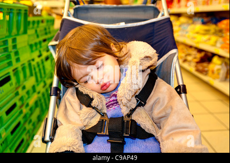 Child asleep in baby carriage - Stock Photo