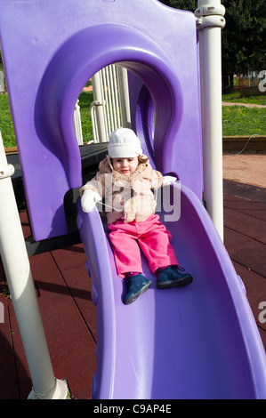 Little child playing on a playground slide - Stock Photo