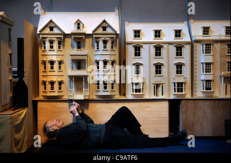 A miniatura enthusiast working on his Pennsylvanian style villa dolls' house at the miniature modelling Show at - Stock Photo