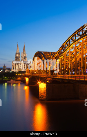 Cologne Cathedral & Hohenzollern Bridge after sunset - Stock Photo
