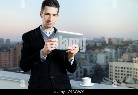 Businessman with a cup of coffee uses a digital tablet on the roof of business center. - Stock Photo