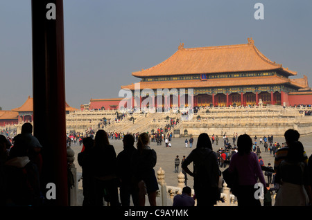 Silhouetted visitors viewing the Hall of Supreme Harmony from the Gate in the Forbidden City Beijing Peoples Republic - Stock Photo