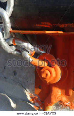 Steel chain painted with red oxide anti rust paint bolted to concrete - Stock Photo