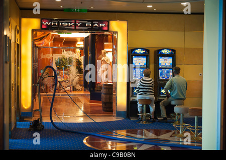A couple playing slot machines beside a vacuum cleaner on the Cruise ship Birka Paradise casino - Stock Photo