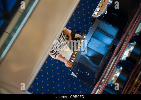 Woman playing a slot machine on the Cruise ship Birka Paradise casino - Stock Photo