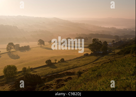 High scenic rural view (Baildon Moor to Hawksworth) of early morning mist over valley farmland & steep wooded hillsides - Stock Photo