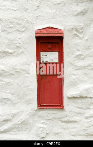Close-up of Royal Mail post box set into a whitewashed wall - it is a rare type of flap opening post box (Hubberholme, - Stock Photo