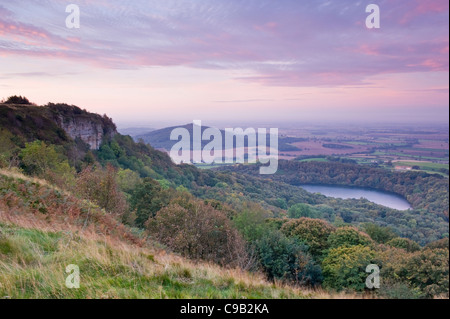 Beautiful scenic long-distance view over Lake Gormire, Hood Hill, Whitestone Cliff & countryside sunrise - Sutton Bank, North Yorkshire, England, UK. Stock Photo