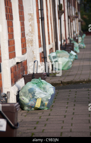 Recycling bags and food waste caddies lined up outside row of terraced houses Roath Cardiff Wales UK - Stock Photo