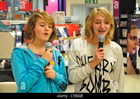Teenage girls singing karaoke in Boots store at Christmas, Kingston upon Thames, Greater London, England, United - Stock Photo
