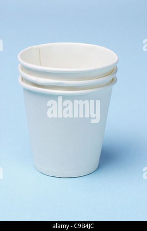 Stack of disposable paper cups on blue background - Stock Photo