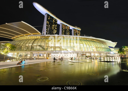 The Marina Bay Sands Hotel and it shopping mall, the Shoppes at Marina Bay as seen during the night. - Stock Photo