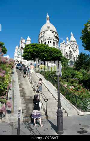 Built in white travertine, Sacre-Coeur Basilica sits on the top of the Butte Montmartre in the French capital Paris - Stock Photo