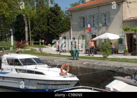 At the écluse de Peyruque, the lock-keeper Jean-Pierre helps houseboat captains in passing the lock on the Canal - Stock Photo
