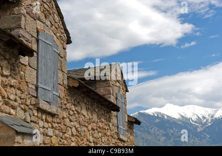 Gables of a natural stone building of Fort Liberia in Villefranche-de-Conflent with view of snow-capped Canigou - Stock Photo
