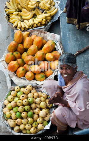 Old Indian woman selling guava, papaya and bananas on the streets of India - Stock Photo