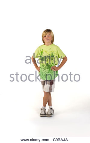 boy age 12 in shorts and a green t-shirt standing on a white background - Stock Photo
