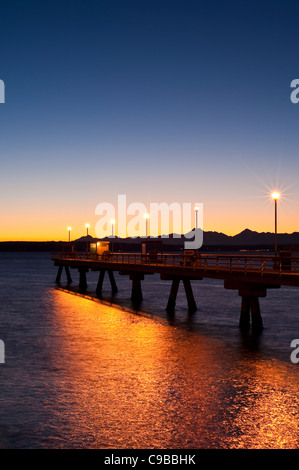 Silhouetted pier with people fishing off dock at sunset on Puget Sound with Olympic mountains - Stock Photo