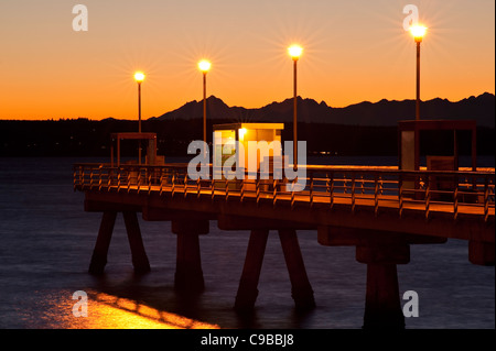 Silhouetted pier with people fishing off dock at sunset on Puget Sound with Olympic mountains Edmonds Washington - Stock Photo