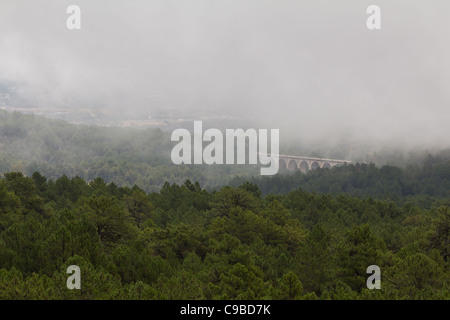 A bridge in the valley of fallen heroes (close to Madrid, Spain) in the fog - Stock Photo