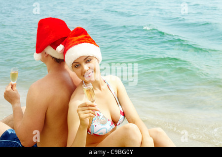 Portrait of female in bikini and Santa cap holding champagne flute and looking at camera on the beach with her husband - Stock Photo