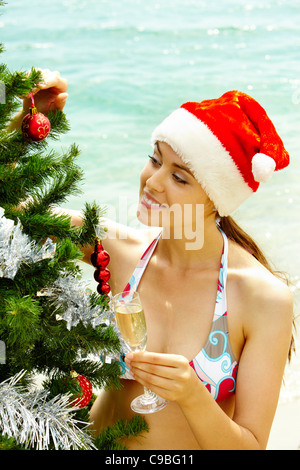 Portrait of female in bikini and Santa cap holding champagne flute and looking at decorated firtree on the beach - Stock Photo