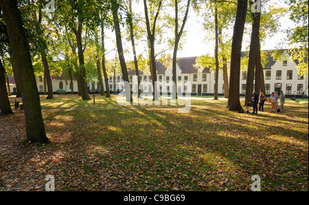 Artists painting on the green in the walled 13th century Begijnhof or Béguinage, in Bruges, Belgium. - Stock Photo