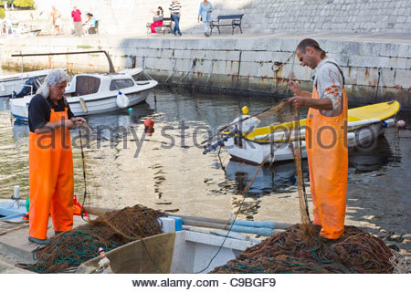 Fishermen preparing nets in the walled city old Dubrovnic, Croatia. - Stock Photo