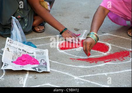Indian girls making a Rangoli Dasara festival design in an Indian street. Puttaparthi, Andhra Pradesh, India - Stock Photo