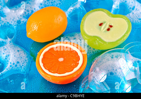 Three soaps in the shape of a lemon, orange, and apple in soap bubbles on a shiny watery blue background - Stock Photo