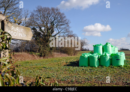 Public Footpath sign and bagged Biosolids contents derived from sewage by Nutri Bio part of Anglian Water stacked - Stock Photo