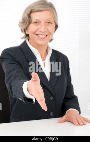 Happy senior successful businesswoman giving handshake close deal - Stock Photo
