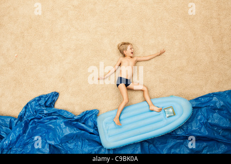 Germany, Boy on inflatable raft in water at beach - Stock Photo