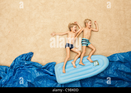 Germany, Boys on inflatable raft in water at beach - Stock Photo