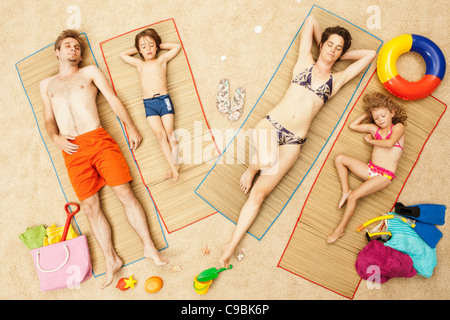 Germany, Artificial beach scene with family lying on mat - Stock Photo
