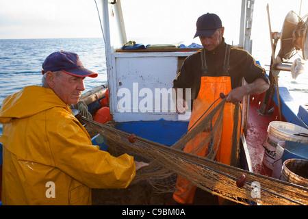 Fishermen reeling in nets on boat - Stock Photo