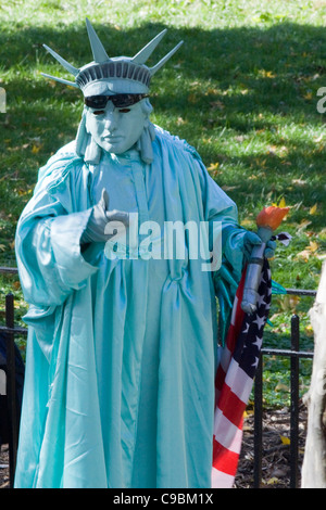 Person dressed as the Statue of Liberty for the Tourists in New York City in Battery Park USA - Stock Photo